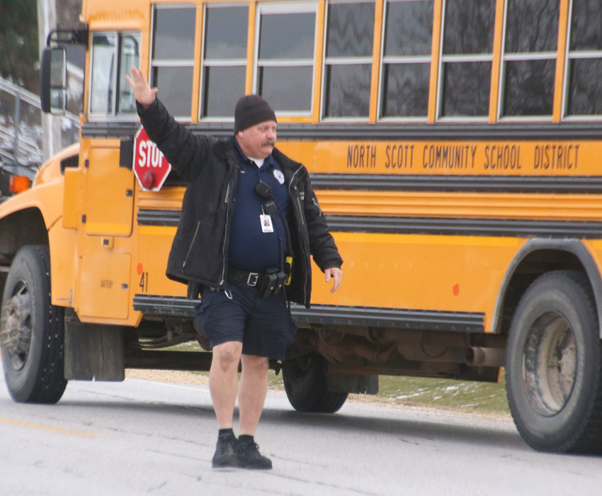 North Scott school resource officer Bruce Schwarz, notorious for wearing shorts no matter the weather, directs traffic while buses leave the parking lot at the end of the day.