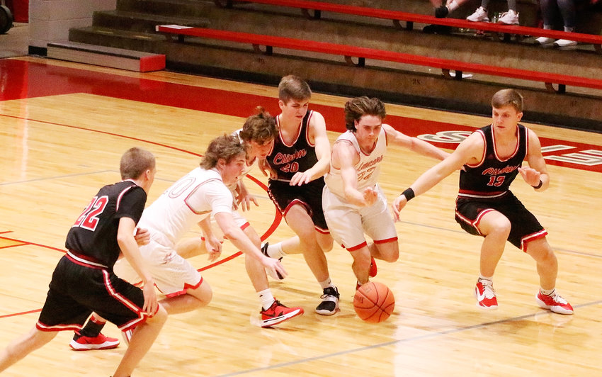 Looking more like they were chasing a fumble in football, North Scott's Cole Kilburg (l), Oliver Hughes and Carter Markham (22) went after this loose ball Friday night. Markham, an all-state quarterback, came up with it and converted a break-away layup.