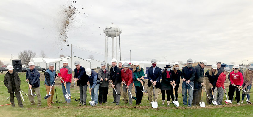 Eldridge council and North Scott school board members lead a ceremonial shovel-throw marking the start of construction of the North Scott YMCA, due to open in March 2022.