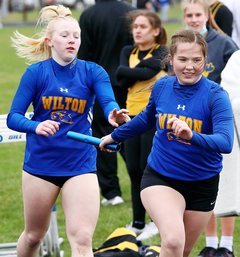 Wilton's Tessa Bartell (left) hands the baton off to Emi Coss during relay action in Wapello March 30.