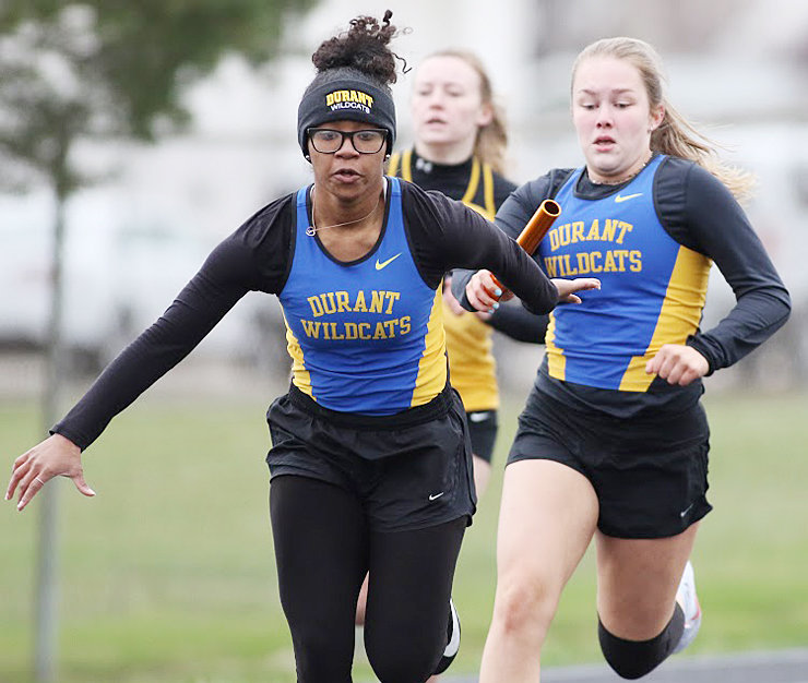 Durant's Lauryn Tate (left) takes a handoff from Dayna Maiers during relay action in Wapello March 30. The Wildcats finished second overall in the team standings with 121.5 points.