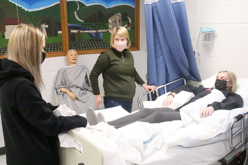 """North Scott High School nurse Emily Dimmer gives a demonstration to one of her CNA classes at the school. The """"patient"""" is Brooklyn Harvey."""