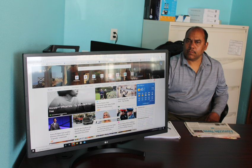 Setting up his new West Liberty office is Jose Salgado, showing a screen that faces his customers as he works out details for their insurance coverage. The giant monitor helps build trust with this clients, knowing exactly what they're buying. The new office is slated to open Monday, May 3.
