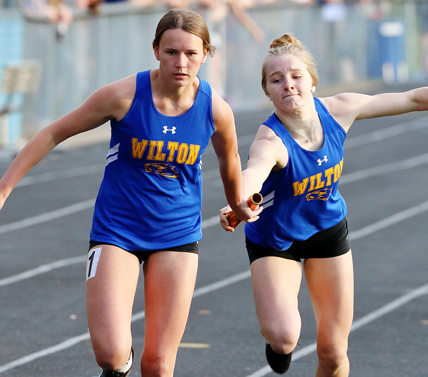 Wilton's Catie Hook (left) takes a handoff from Hannah Rogers in relay action.
