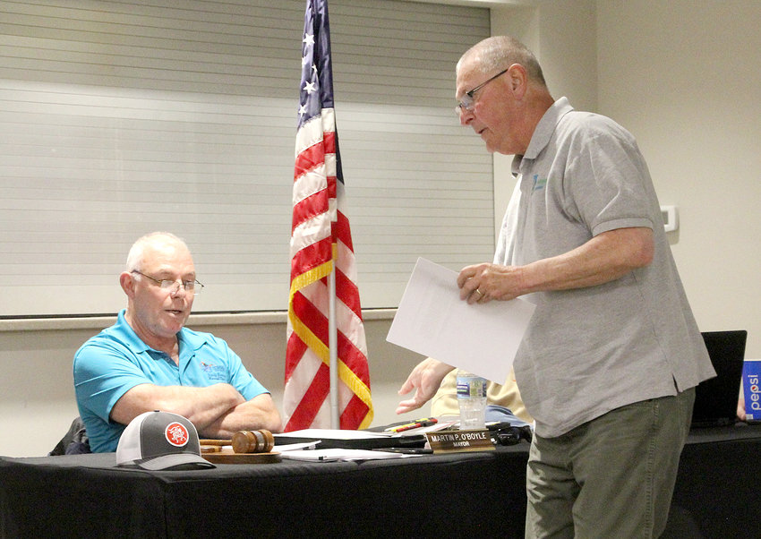 Eldridge council member Bruce Cheek, right, hands out a memo to Mayor Marty O'Boyle and council members threatening an Iowa Attorney General investigation into city police records.
