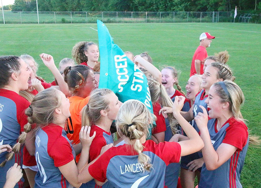 Members of North Scott's girls' soccer team were all smiles after they collected their state qualifier banner from athletic director Jason Schroeder.
