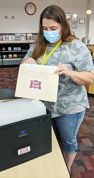 """Ashly Carter, librarian at the Wilton Public Library, peruses the Rock Island Railroad information file recently acquired from an anonymous donor. The file includes computer-printed photos, mechanical diagrams, magazine articles and maps, all pertaining to the Chicago Rock Island and Pacific Railroad dating from the 1900s to 1950s. The Rock Island material is available for viewing at the library at any time. The Wilton Public Library is open to the public with limited access to computers. Facemasks are required while inside. The library is not currently able to have in-person programming, but is continuing the """"Take and Make"""" crafts which are paper lunch bags with everything one needs to take home and make a craft. The library also offers """"Story Time in a Bag"""" which consists of books, activity sheets, and a craft. There are also fun activities on the website www.wilton.lib.ia.us like a virtual escape room, Harry Potter trivia, and other digital adventures. The Friends of the Library fundraiser is still working toward a $5,000 goal to help purchase a new server for the library. If anyone would like to help with a donation, they can stop by the library, or send their donation to Friends of the Wilton Public Library, PO Box 447, Wilton IA 52778."""