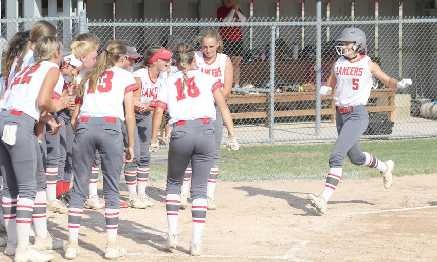 Lancer sophomore Teagan Kelley is greeted by her teammates after stroking a two-run homer in the first game of North Scott's scheduled doubleheader with Bettendorf on Thursday. The Lancers were leading 4-0 when the game was suspended by weather entering the seventh inning. It will be made up on Thursday.