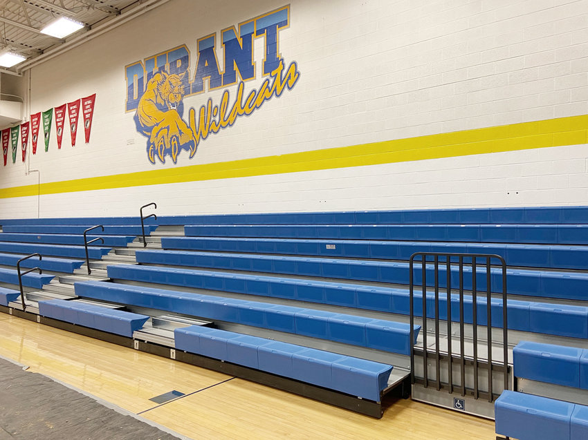 New blue plastic resin bleachers were recently installed in the Durant High School gymnasium, replacing the original wooden bleachers in use since the 1970s. The south end storage room is being converted into a new concession stand as well. Shown are several photos of the ongoing construction of the new concession stand and the bleachers.