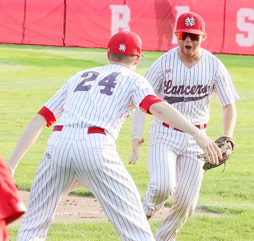 Noah Young celebrates his first-inning catch in right field with teammate Alex Dickman (24).