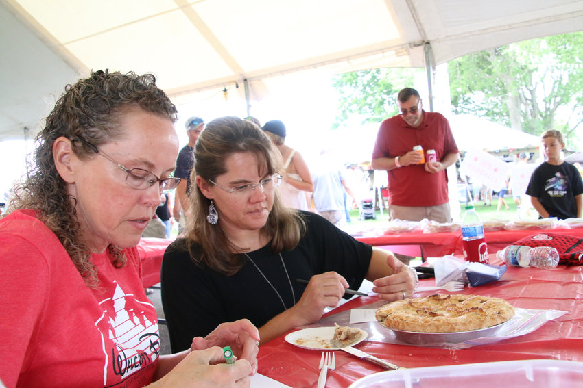 Pie contest judges Carrie Keppy and Kim Powell sample a thin slice from each of the 41 entries.