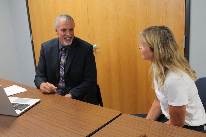 West Liberty School Board President Emily Geertz visits with new Superintendent Shaun Kruger in his first board meeting last week.