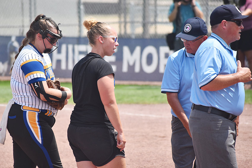 Wilton starting pitcher Mila Johnson and head coach Kortney Denkman meet with umpires after Johnson was called for several illegal pitches in the state semifinal game with Earlham July 21.