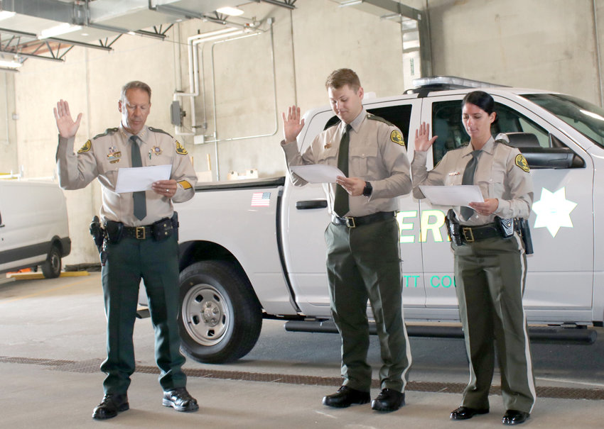 Scott County Sheriff Tim Lane swears in new deputies Landon Slagle and Samantha Johannes, Aug. 16 at the patrol station in Eldridge.