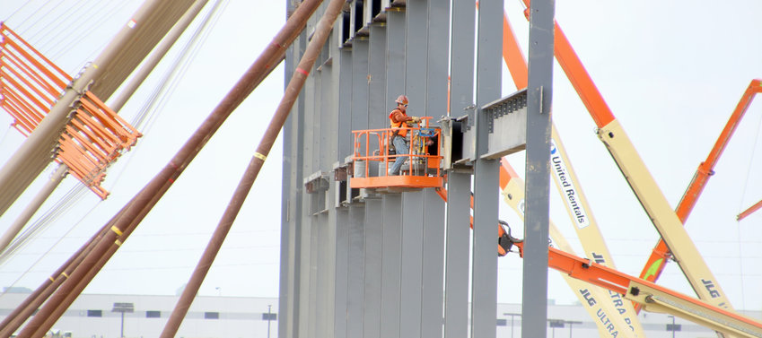 Workers connect beams Monday on walls for a 640,000-square-foot Amazon warehouse.