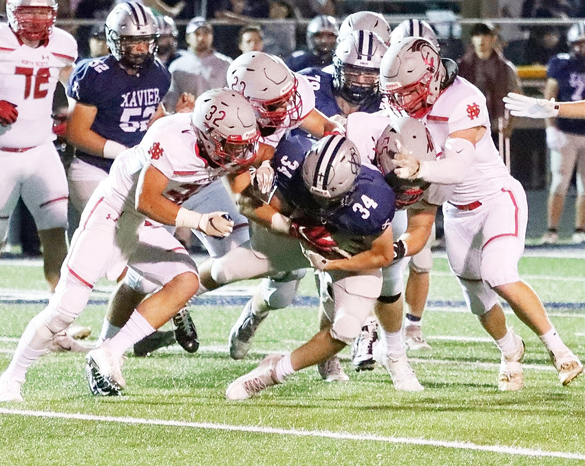 """Playing the """"gang tackle"""" philosophy to perfection, North Scott's dominating defense was in a stingy mood, and Xavier running back Michael Cunningham found little running room all night. Seniors Peyton Kruse (32), Ryan Campbell 23) and Adam Allen (55), along with junior AJ Petersen (right) gave him a rude awakening on this play."""