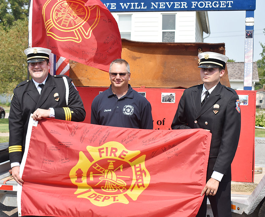 Durant Fire Chief Jared Semsch (middle) is pictured with the flag he signed as the Scott County 9/11 memorial parade came to Durant Sept. 11.