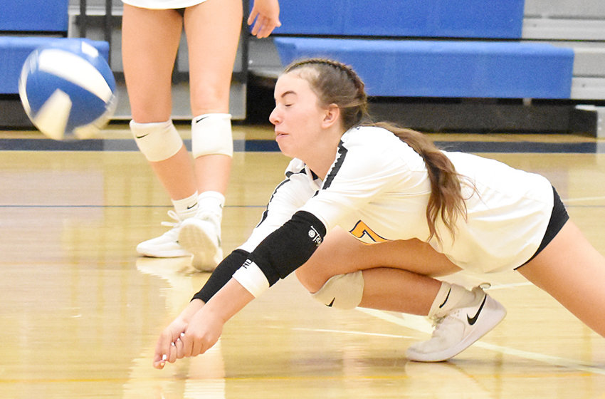 Wilton's Mallory Lange dives for a dig.
