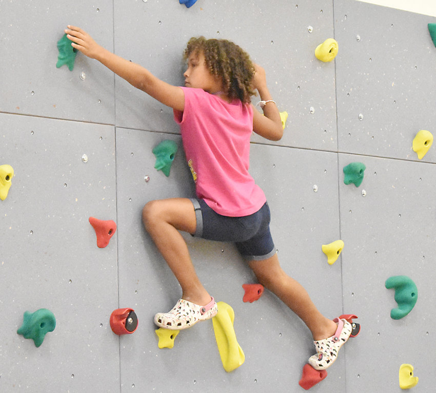 """Wilton Elementary adds a climbing wall—A rock wall was donated to Wilton Elementary School by the Townsend Foundation. According to physical education teacher Jake Souhrada, it is 12-by-40 feet installed in two sections on the east wall of the elementary gym. """"This provides great exercise and fun for the students working on upper body strength,"""" said Souhrada. """"The students really enjoy getting to use this rock wall, it is a huge addition to the elementary PE program. (Maintenance Director) Andy Crawford got the rock wall up with the help of Justin Marston. We climb it every Wednesday."""" Blaze Parker is pictured climbing the wall."""
