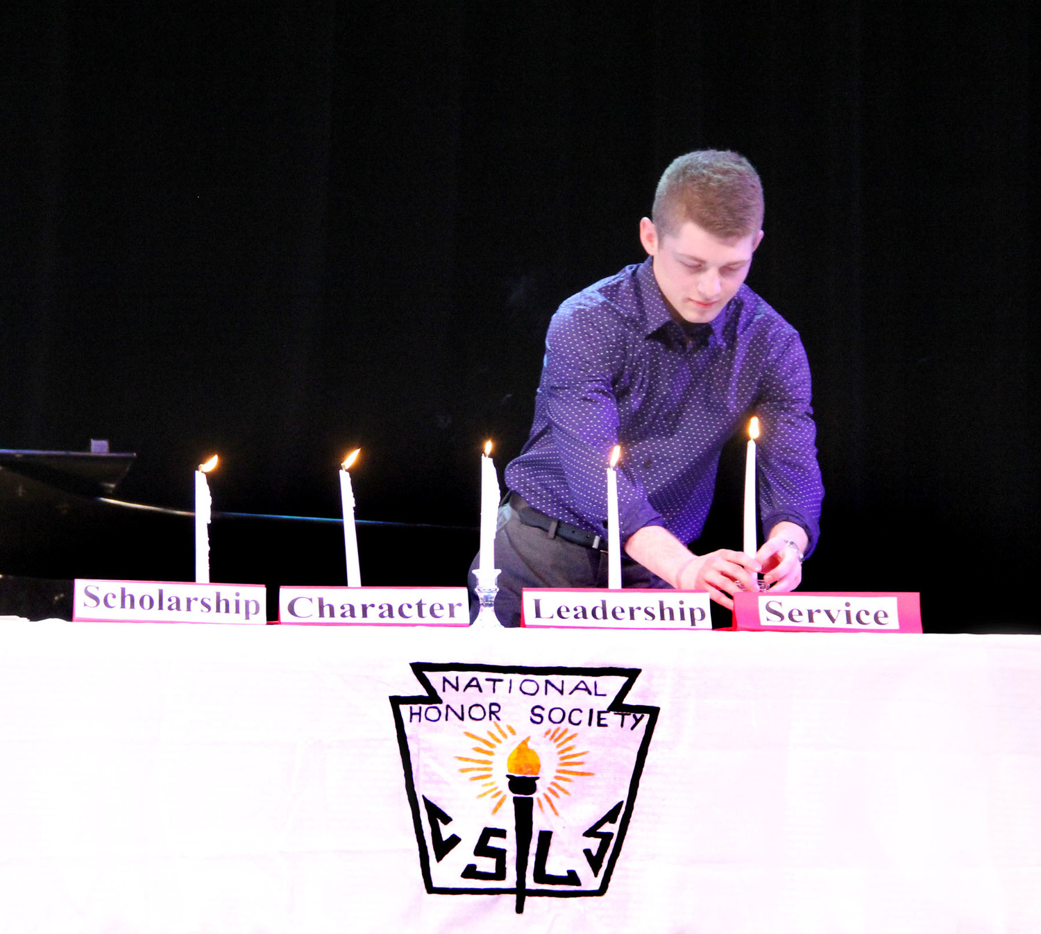 Caleb McCabe lights the service candle.