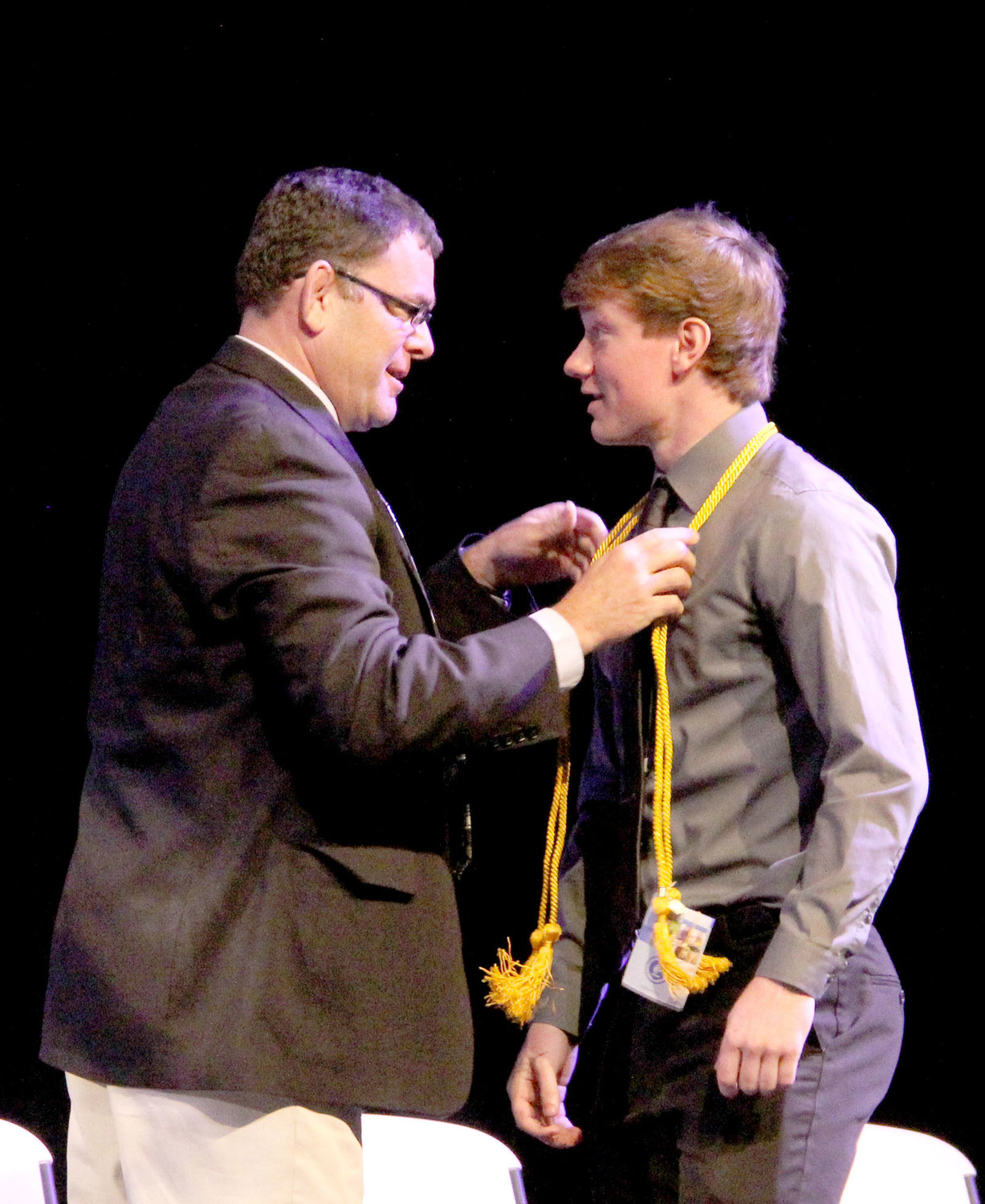 Superintendent Joe Stutting drapes honors cords on Tony Barrecca.