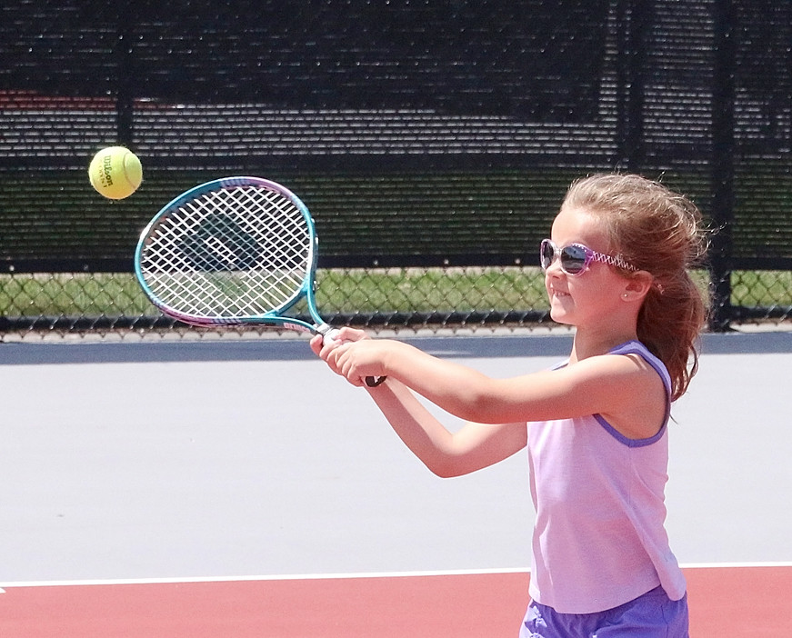 Eden Burt keeps her shaded eyes on the ball while working on her forehand under the tutelage of Lancer boys' tennis coach Todd Satterly.