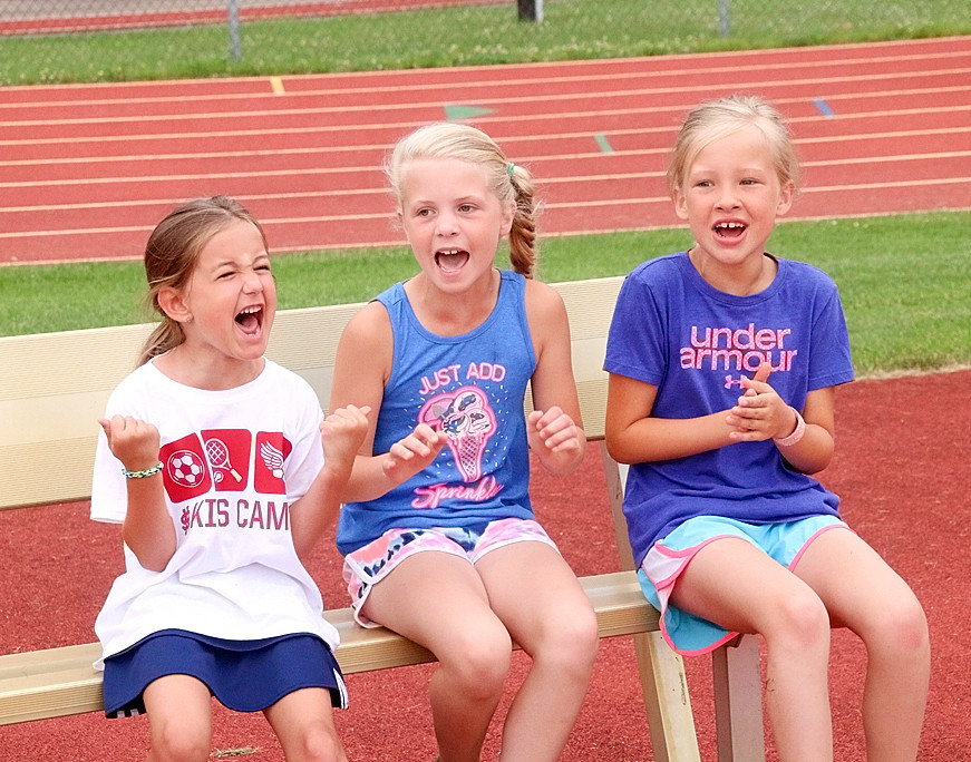 Morgan Keppy, Brinley Schroeder and Sophi Schneckloth cheer on their teammates during a relay race at Lancer Stadium.