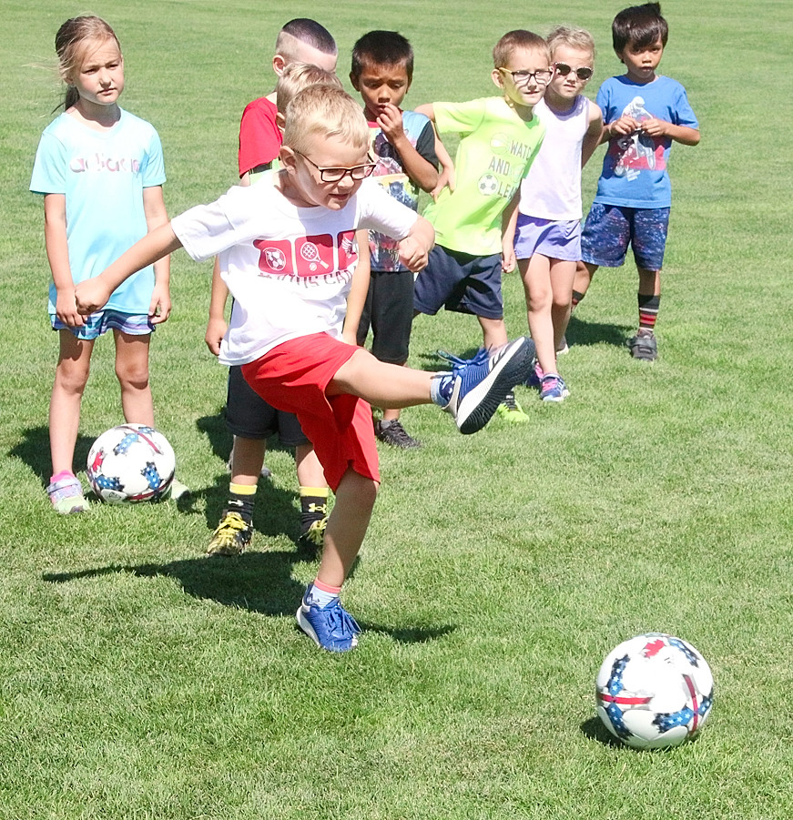 With his fellow campers looking on, Kaiden Lee drills a soccer ball toward the back of the net.