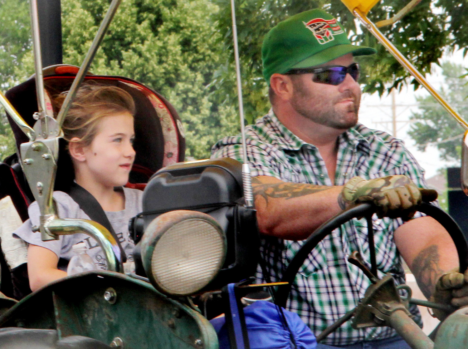 A tractor driver and his daughter leave North Scott High School to continue WHO tractor ride on June 25, 2018.