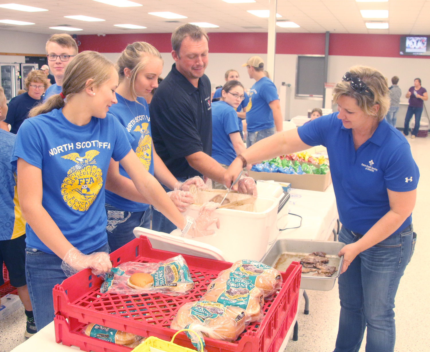 North Scott School Board member Mark Pratt joins FFA volunteers serving lunch at the high school cafeteria for the WHO Tractor Ride, Monday, June 25, 2018.