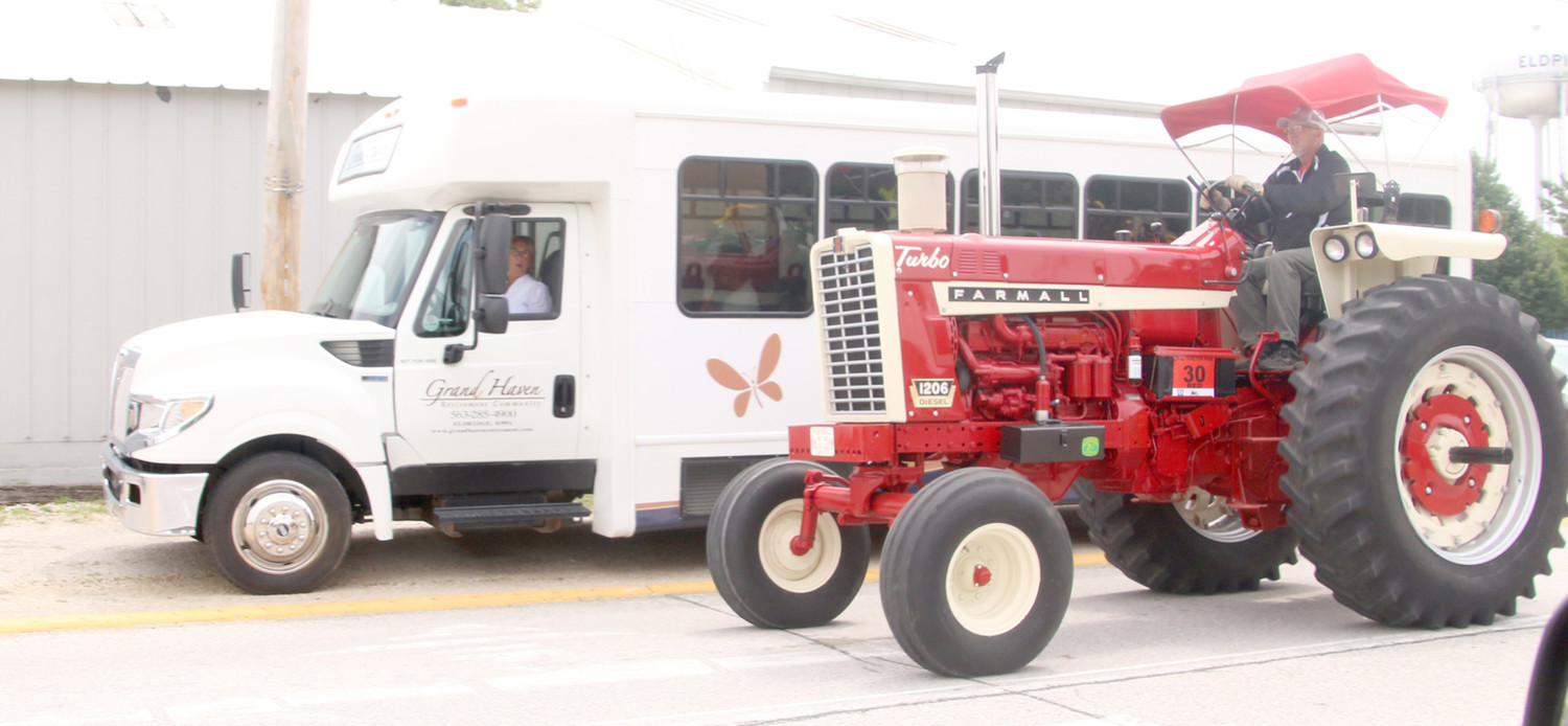 Grand Haven residents enjoy the tractor parade from their bus parked along South First Street.