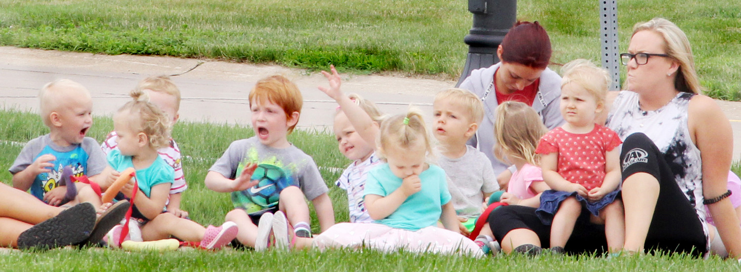 A group of kids gather to watch the WHO tractor ride parade down LeClaire Road on June 25, 2018.