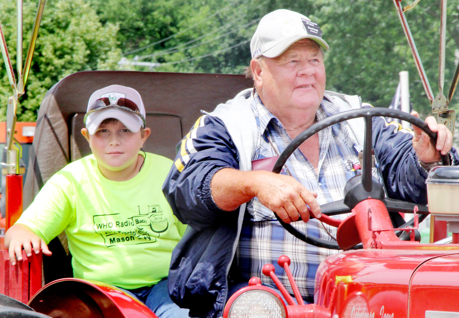Two participants in the WHO tractor ride leave North Scott High School to continue the drive on June 25, 2018.