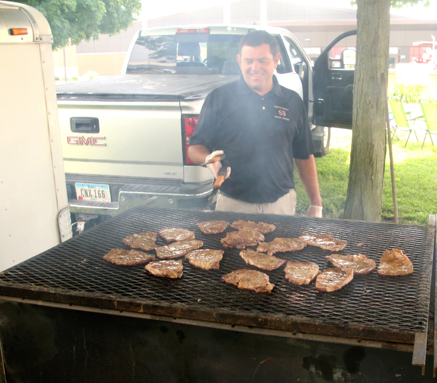 North Scott Schools Superintendent Joe Stutting grills ribeyes for the WHO Tractor Parade crowd gathered at the high school, June 25, 2018.