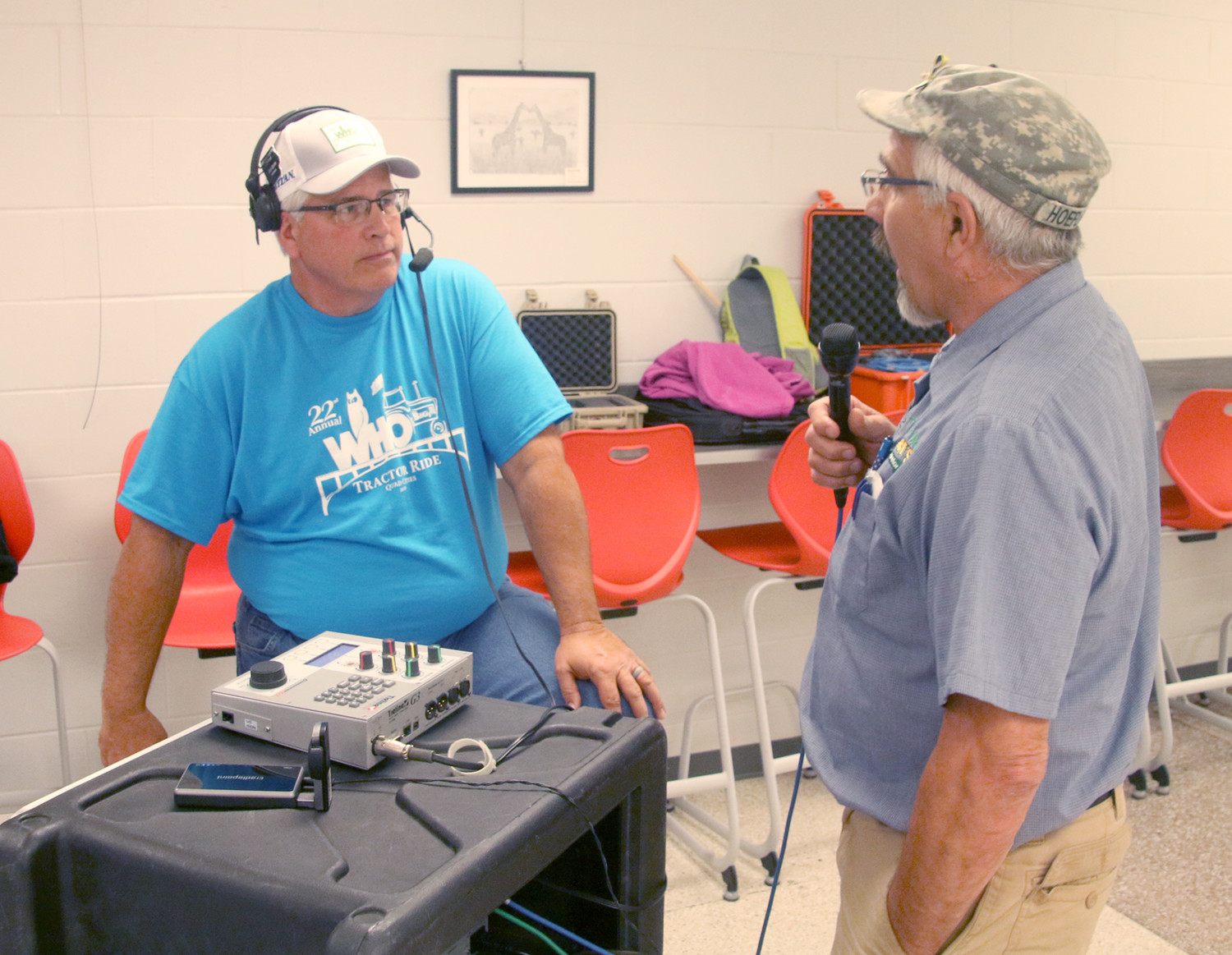 Bob Quinn, of WHO, interviews Tractor Ride sponsor Gary Hoefling, who owns Roberts Carburetor Repair in Spencer, at the North Scott High School cafeteria.