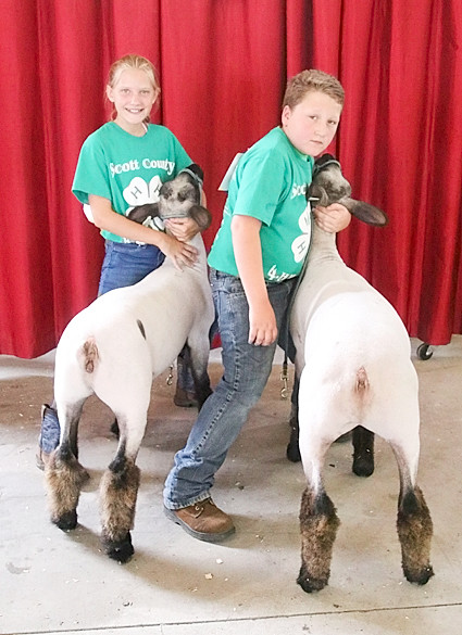 Kylie Klindt (l) showed the Reserve Champion Pair of Market Lambs. Helping her is Joey Porter.