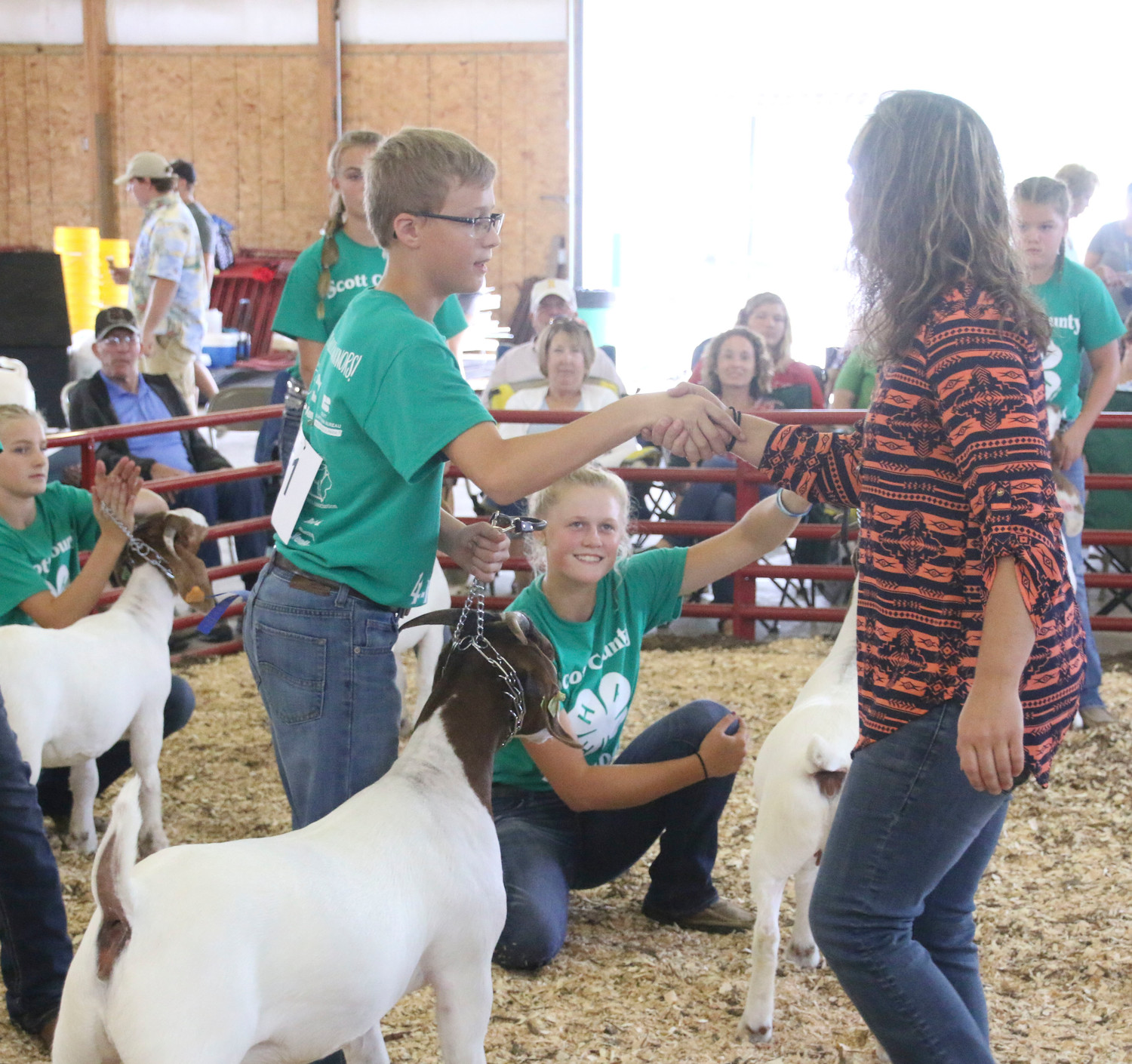 Caden Meyer receives congratulations from judge Ashley Wiebe during the Meat Goat show.