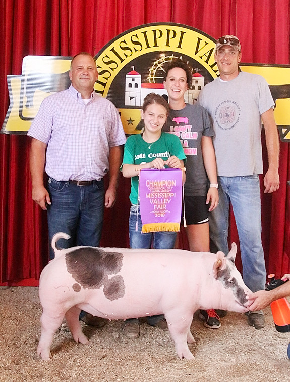 Bella Buesing showed the Champion Commercial Gilt. She's pictured with Judge Ty Egnell (left) and her parents, Dana and Justin.