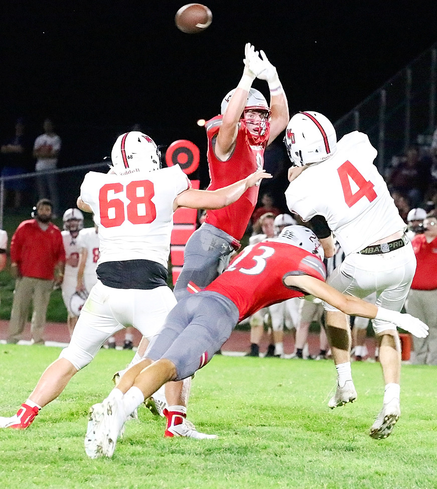 Juniors Zach Campbell (23) and Ben Belken (8) pressure Western Dubuque quarterback Calvin Harris into throwing a first-half interception.
