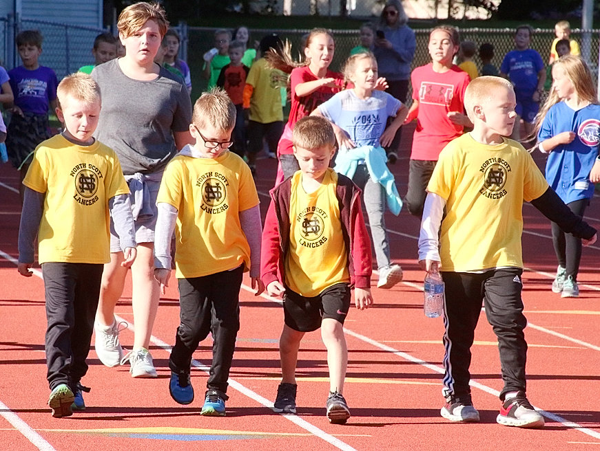 First-graders Coy Sherwood, Cole Sherwood, Leo Nelson and Jaden Kroeger decided the buddy system was the best way to circle the Lancer Stadium track.