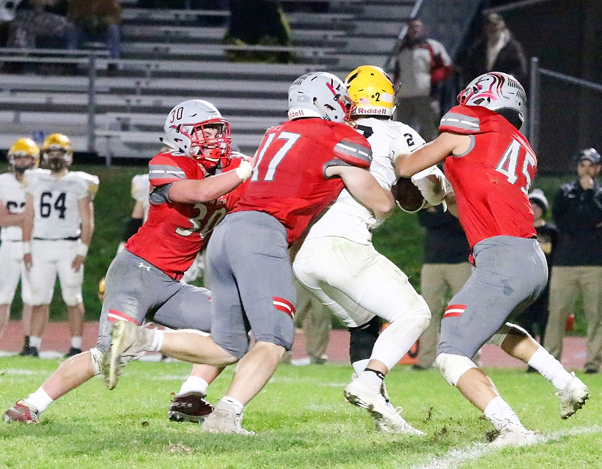 Mason Watts, Griffin Wilder, and Sam Erickson gang up on WSR quarterback Luke Velky.