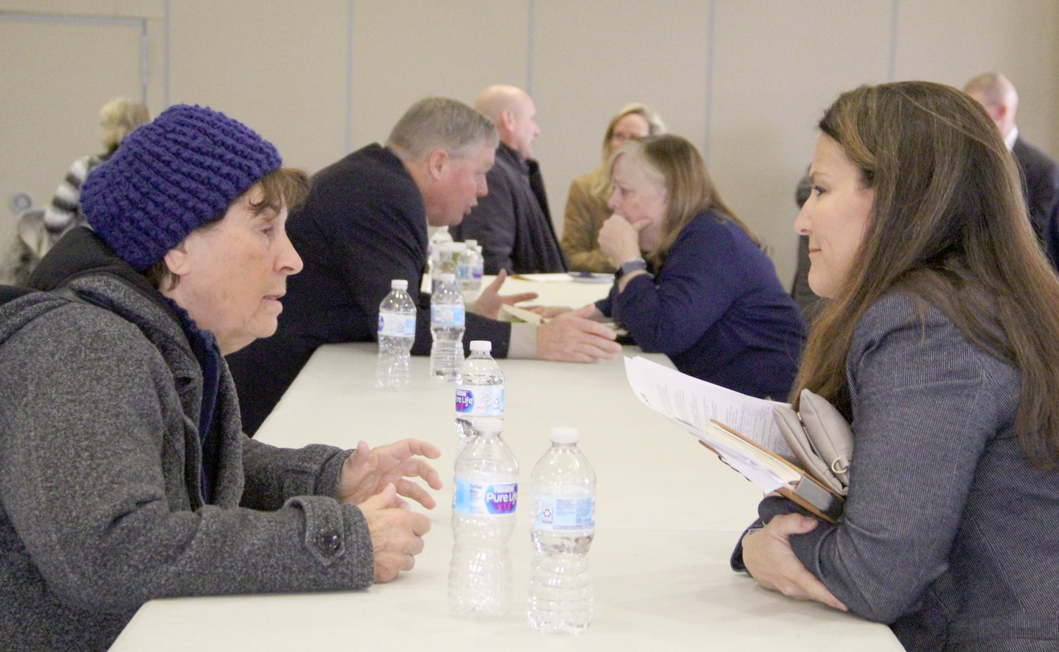 Sen. Chris Cournoyer, front right, and Rep. Monica Kurth, back right, talk with residents after the forum.