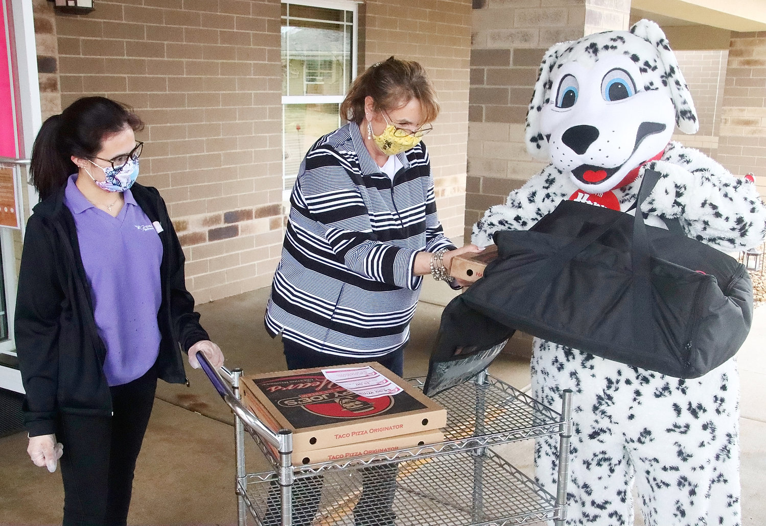 Grand Haven employees Masie Knutsen and Jennifer Maas greet Happy the Dog (aka Alaina Woods, right) outside Grand Haven and are happy to take 14 sausage and pepperoni pizzas for isolated residents.