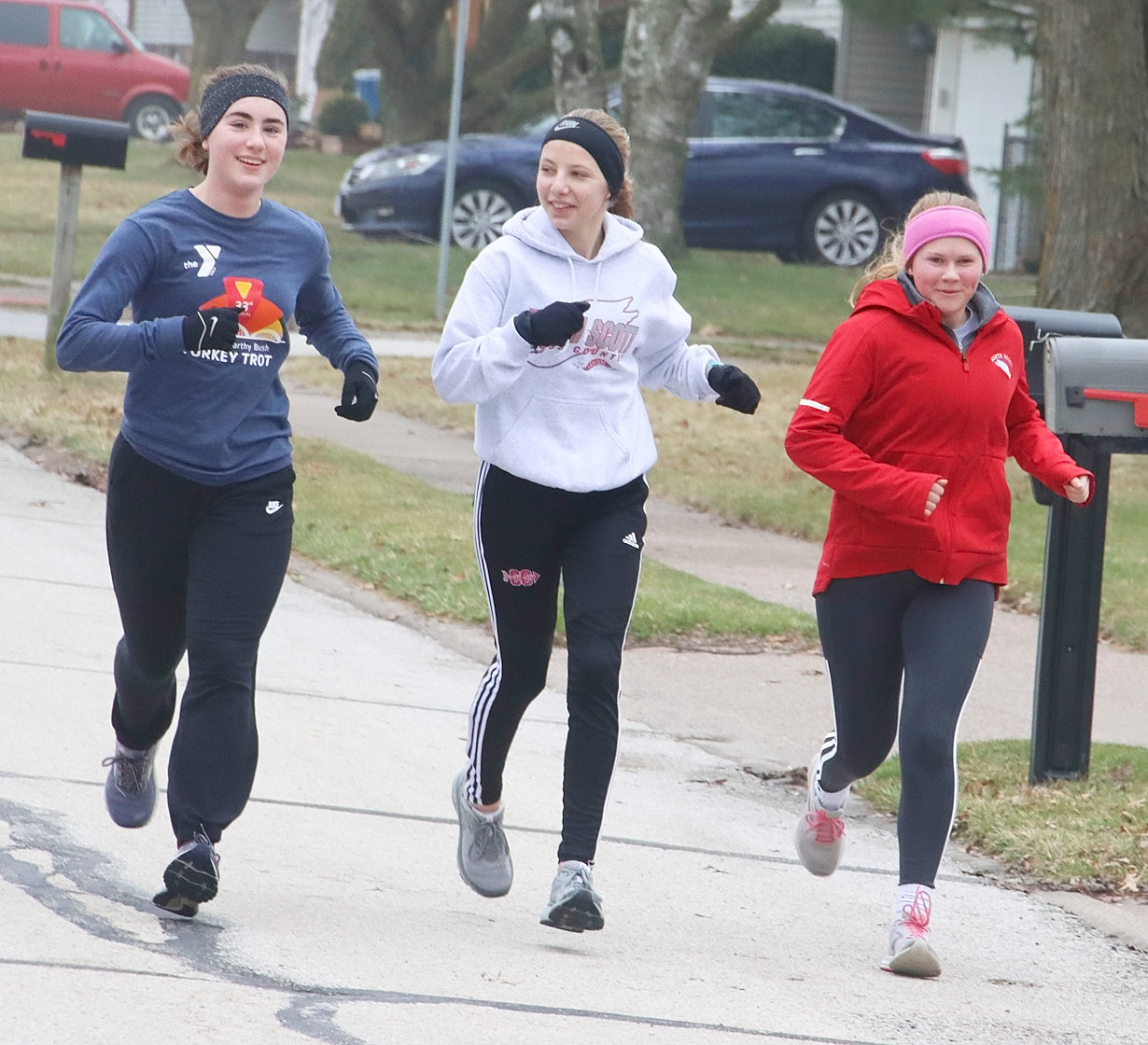 Ava Garrard, Kaitlyn Knoche and Sadie West, all members of North Scott's girls' track team, go on a training run through the streets of Eldridge.