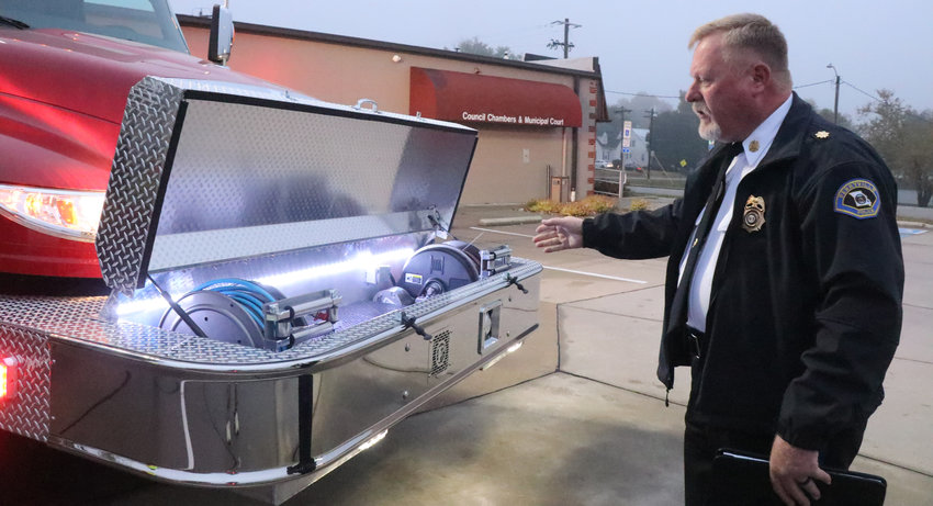 """Perryville Assistant Fire Chief Bill Jones, opens the front bumper to unveil several components of the new heavy rescue truck, which includes the """"jaws of life,""""  before the Board of Alderman meeting on Tuesday. The truck is the newest fire apparatus the fire department has bought since 2006."""