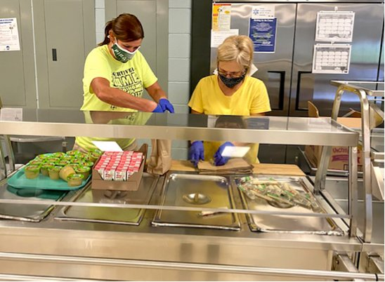 District 32 food service workers Kimberly Seabaugh and Charlotte Colin pack bagged meals for children, who eat free on any school day, either in school or by picking up Grab & Go Meals through the drive-thru line.