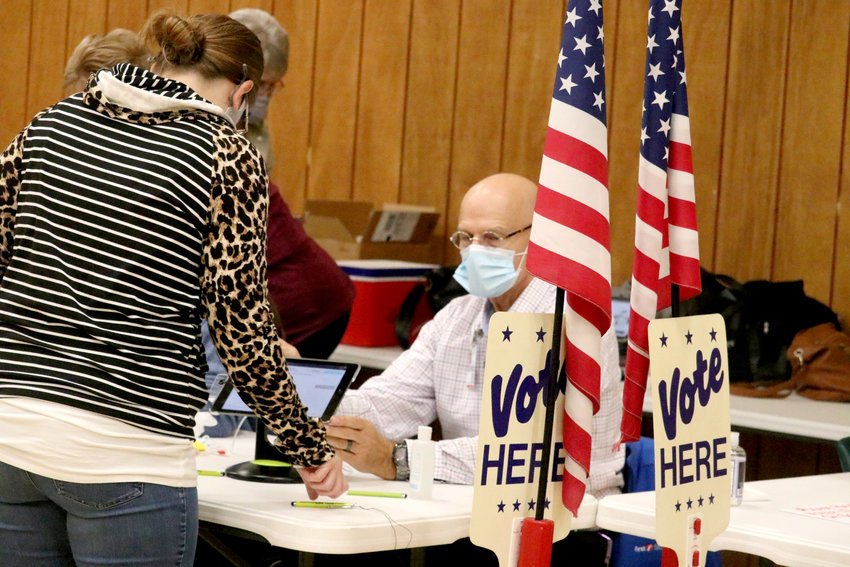Greg Schimpf helps a voter sign in Tuesday morning at the Perry Park Center polling station. The Park Center location, which serves voters in the newly combined precincts of Perryville P-1 and P-4 saw 1,168 total voters. As a whole, Perry County saw a 72.65 percent voter turnout.