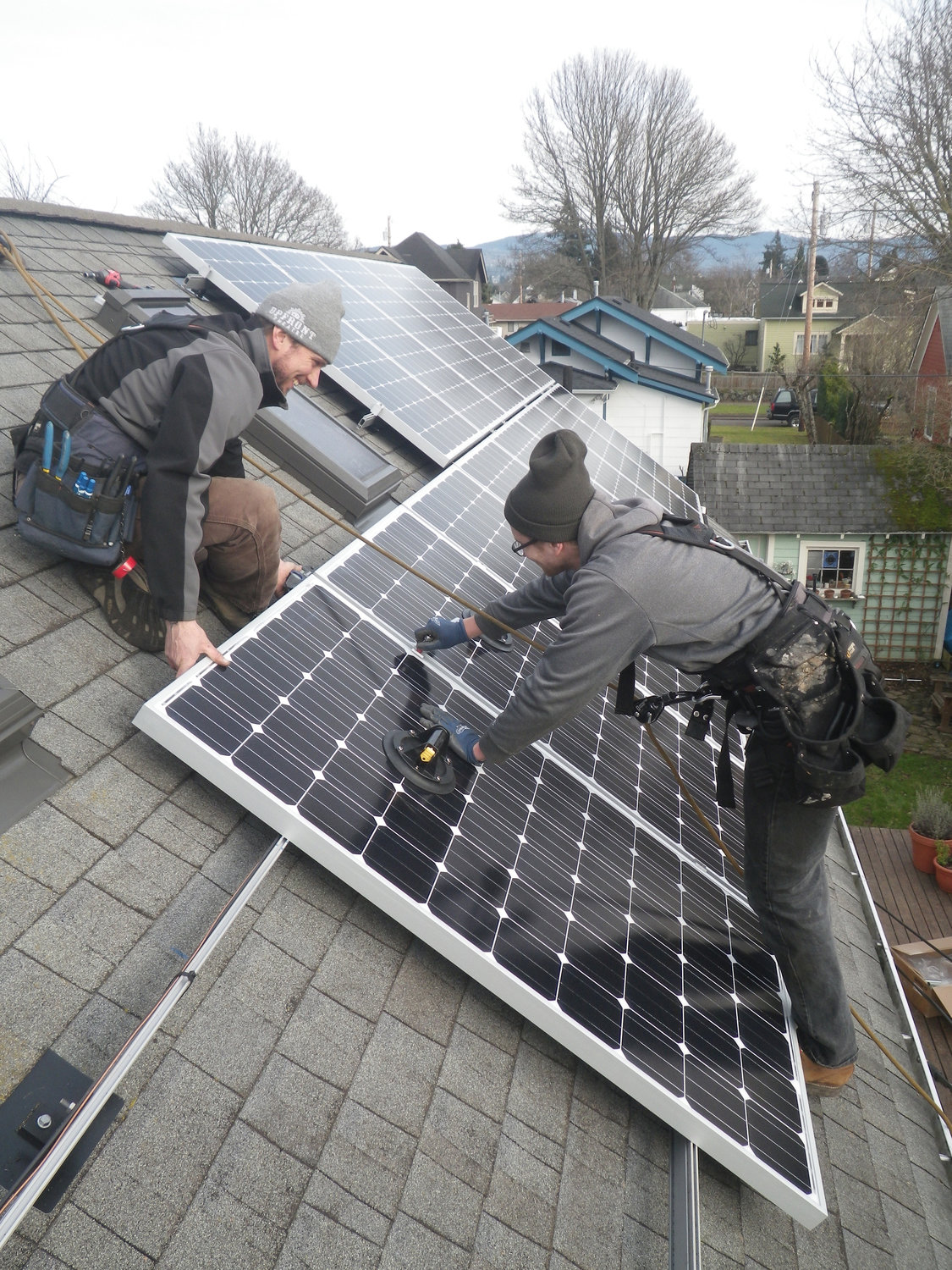 Workers installing solar panels onto the roofs of local homes.