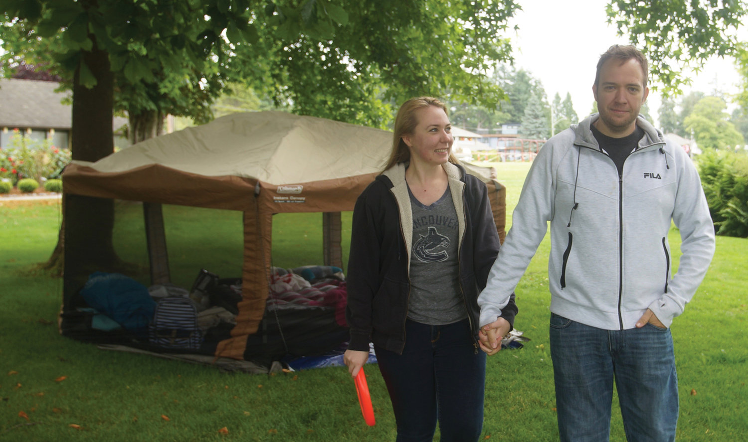"Kaelynn Ball of Surrey, B.C., l., and fiancé David Hogsten of Maryland pose in front of their ""picnic tent"" at Peace Arch Park on Thursday, July 2. The two spent the weekend together at the park, lounging in their tent. ""I'm overjoyed we can still see each other,"" Ball said."