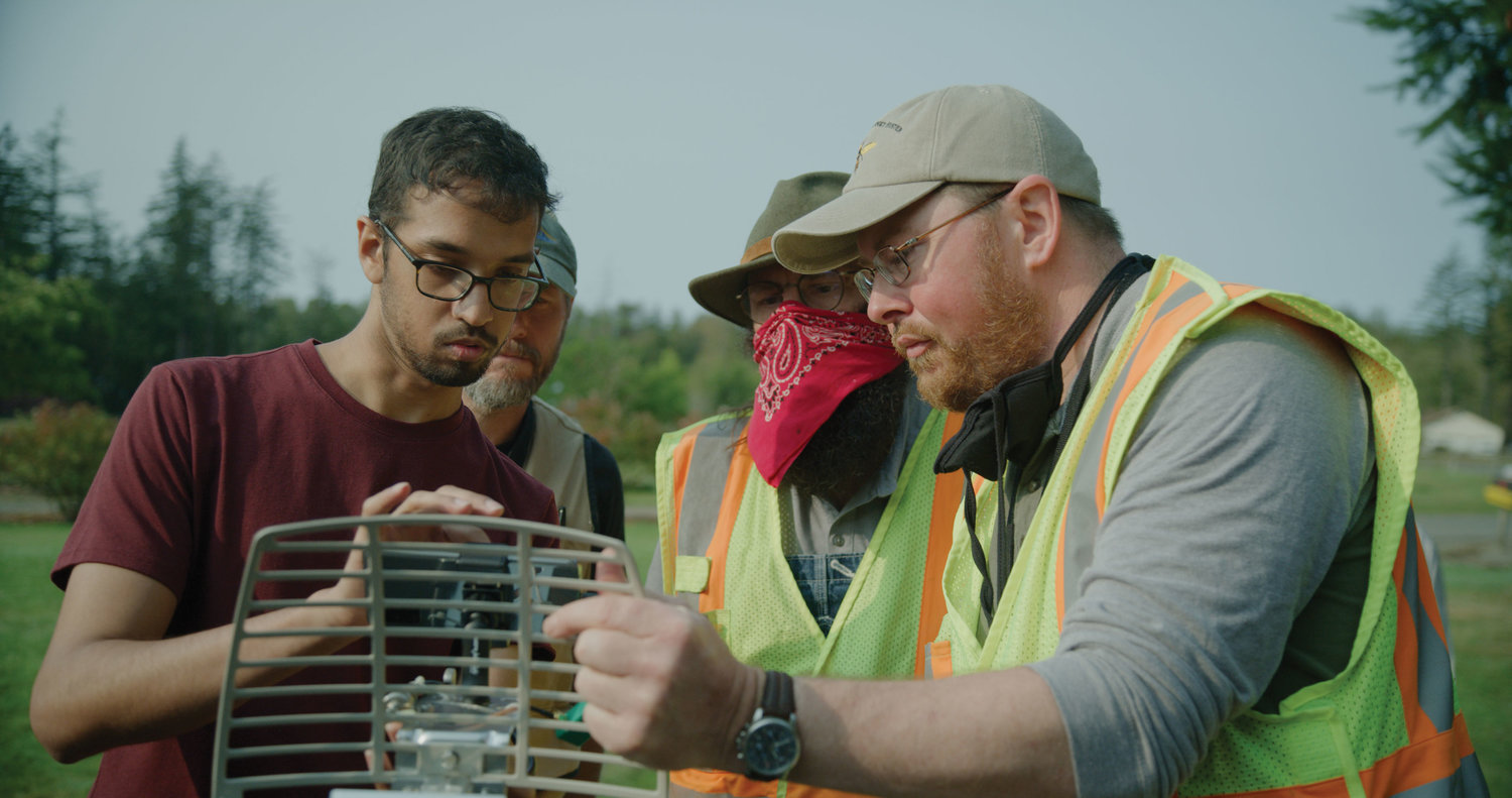 From l., Vikram Iyer, a University of Washington Ph.D. student who created a radio tag to track the Asian giant hornet, shows WSDA entomologist Chris Looney, eradication coordinator Rian Wojahn and managing entomologist Sven Spichiger how to use the device on September 30 in east Blaine.
